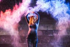 Würfe und Tanz der jungen Frau mit Farbpulver auf dunklem Hintergrund stockfotos