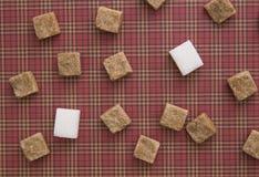 Würfel Browns und des raffinierten Zuckers auf rotem Hintergrund Kopieren Sie Platz Beschneidungspfad eingeschlossen Lizenzfreie Stockfotos