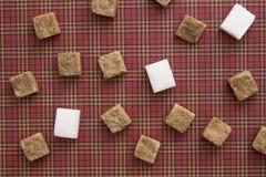 Würfel Browns und des raffinierten Zuckers auf rotem Hintergrund Kopieren Sie Platz Beschneidungspfad eingeschlossen Lizenzfreies Stockfoto