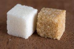 Würfel des braunen und raffinierten Zuckers an Bord von Mahagonibaum Lizenzfreies Stockfoto