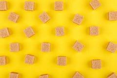 Würfel des braunen Zuckers auf gelbem Hintergrund lizenzfreie stockfotos