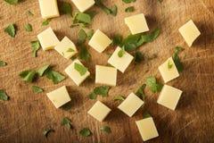 Würfel des gelben Käses mit den Kräutern nach dem Zufall gestapelt Lizenzfreie Stockfotografie