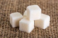 Würfel des raffinierten Zuckers auf Jutefasertaschen Stockbild