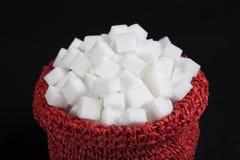 Würfel des raffinierten Zuckers in einer roten Tasche Stockbild