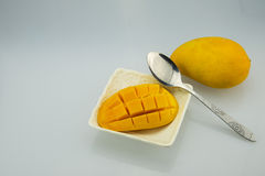 Würfel einer weißen Platte, des Löffels und der Mango Lizenzfreie Stockbilder