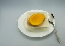 Würfel einer weißen Platte, des Löffels und der Mango Stockfotografie