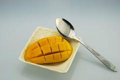 Würfel einer weißen Platte, des Löffels und der Mango Lizenzfreie Stockfotografie