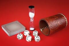 Würfel, Karten und lederne Schale auf rotem Hintergrund Lizenzfreie Stockfotos
