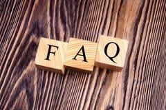 Würfel mit einem Aufschrift FAQ auf den alten Brettern lizenzfreies stockfoto