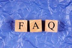 Würfel mit einem Aufschrift FAQ auf Veilchen zerknitterten Papier stockbild
