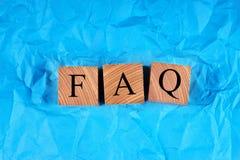 Würfel mit einem Aufschrift FAQ auf zerknittertem blauem Papier stockbilder