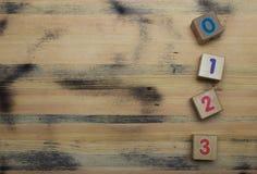 Würfel mit Zahlen auf hölzernem Hintergrund Lizenzfreies Stockbild