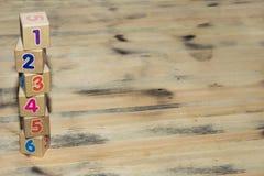 Würfel mit Zahlen auf hölzernem Hintergrund Lizenzfreie Stockbilder