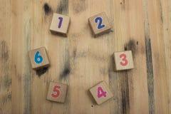Würfel mit Zahlen auf hölzernem Hintergrund Stockbild
