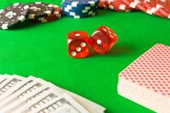 Würfel, Pokerchips und 100 Dollarscheine auf der grünen Tabelle E Lizenzfreie Stockbilder