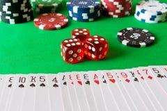 Würfel, Pokerchips und Spielkarten auf der grünen Tabelle Spiel Co Lizenzfreie Stockfotografie