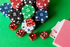 Würfel, Pokerchips und Spielkarten auf der grünen Tabelle Spiel Co Stockbilder