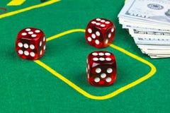 Würfel rollt auf einem Dollarscheine Geld Grüne Pokertabelle am Kasino Pokerspielkonzept Spielen eines Spiels mit Würfeln Kasinow Stockfotografie