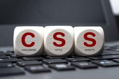 Würfel und Würfel auf Laptoptastatur mit Kaskadenformatvorlagen CSS stockfoto