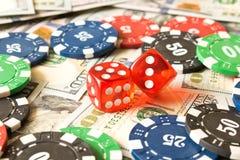 Würfel und Pokerchips auf dem Hintergrund von zerstreut 100 Rechnungen W Lizenzfreies Stockfoto