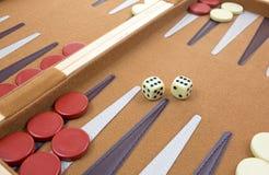 Würfel und Stücke des Backgammonspiels Stockfotografie
