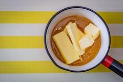 Würfel von Butter eingebettet im Honig in einer Kasserolle bereit, für das Backen erhitzt zu werden lizenzfreie stockfotografie