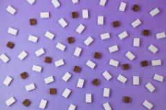 Würfelmuster Browns und des raffinierten Zuckers auf violettem Hintergrund Stockfotografie