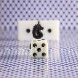 Würfeln Sie auf dem unscharfen Hintergrund des Schachdominos und der Rückseite der Spielkarten Lizenzfreie Stockfotografie