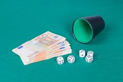 Würfelt mit Schale und Euros auf grünem Stoff Lizenzfreie Stockfotografie