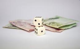 2 würfelt mit thailändischem Geld Stockbild