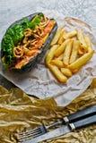 Würstchen mit Rindfleischwurst und karamellisierten Zwiebeln in einem schwarzen Brötchen Grauhintergrund, Seitenansicht lizenzfreie stockfotos