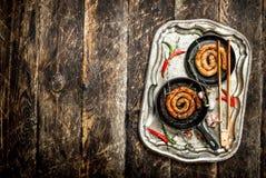 Würste in den Wannen auf einem Stahlbehälter mit scharfem Paprika pfeffert Stockfoto
