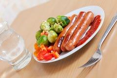 Würste mit Brokkoli auf weißer Platte Lizenzfreies Stockbild