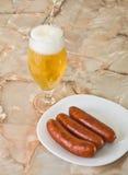 Würste mit einem frischen Bier lizenzfreies stockfoto