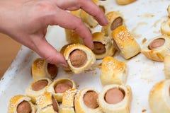 Würste rollten im gebackenen Abkühlen des Hörnchens Teig auf Metallgestell Lizenzfreie Stockbilder