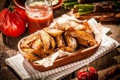 Würzige Kartoffelkeile mit frischem Tomatensaft Lizenzfreies Stockbild