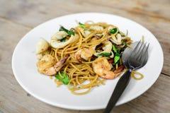 Würzige Spaghettis mit Meeresfrüchten auf Holztisch Stockfotografie