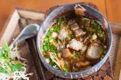 Würzige TOM YAM-Nudelsuppe mit knusperigem Schweinefleisch Stockfoto