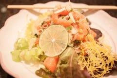 Würziger Lachssalat auf weißer Platte Stockfotos