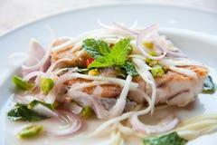 Würziger Salat mit gebratenen Fischen und grünem Kraut in siamesischem Stockbilder