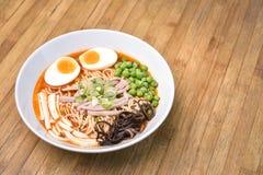 Würziger Tom Yum, sahnige Schweinefleisch Ramen mit Ei, Sugar Pea, Tofu und M Lizenzfreies Stockfoto