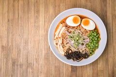 Würziger Tom Yum, sahnige Schweinefleisch Ramen mit Ei, Sugar Pea, Tofu und Pilz auf hölzernem Hintergrund Lizenzfreie Stockfotos