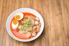 Würziger Tom Yum, sahnige Schweinefleisch Ramen mit Ei und Pilz auf Holz b Lizenzfreie Stockfotos