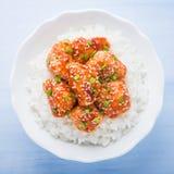 Würziges süßes und saures Huhn mit indischem Sesam und Reis auf Draufsicht des blauen hölzernen Hintergrundes Lizenzfreies Stockfoto