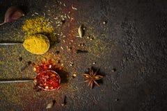 Würzt Lebensmittelhintergrund Auswahlvielzahl trockene ganze und Grundgewürze auf einem schwarzen Hintergrund Stockfoto