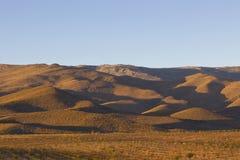 Wüstenberge mit langen Schatten bei Sonnenuntergang Stockfotos