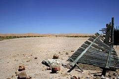 Wüstenlandschaft mit unterbrochenem hölzernem Pfostenzaun Lizenzfreies Stockfoto