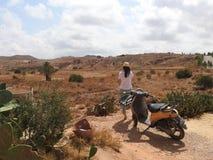 Wüstenlandschaft und klarer Himmel, eine Frau in einem Hut, der den Abstand, Foto von der Rückseite untersucht, stellen nicht sic stockfotografie