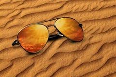 Wüstensand und Sonnenbrille-Reflexions-Ferien-Konzept Stockfotos