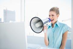 Wütende elegante Frau, die im Megaphon schreit Stockbilder